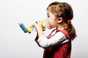 little girl doing inhlation using her inhaler